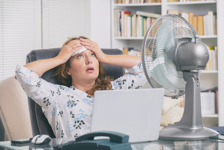 Woman suffers from heat while working in the office and tries to cool off by the fan.