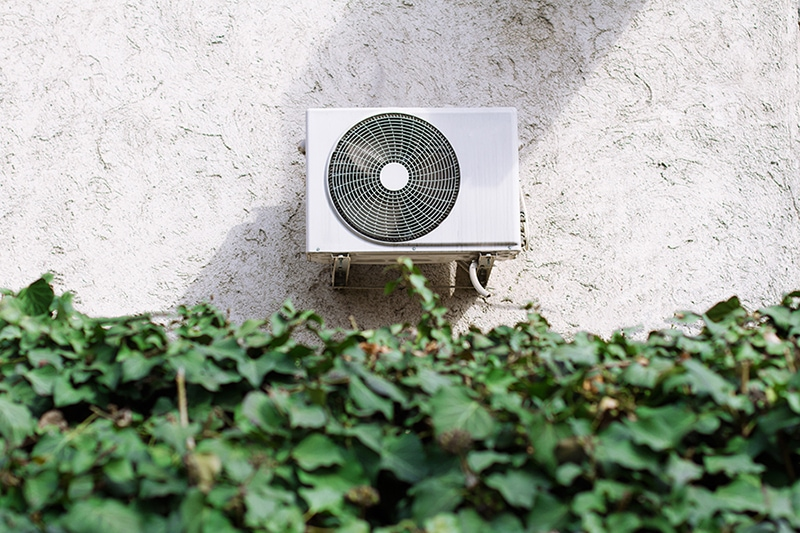 horizontal front view of a white air conditioning unit behind a decorative garden wall of green leaves.