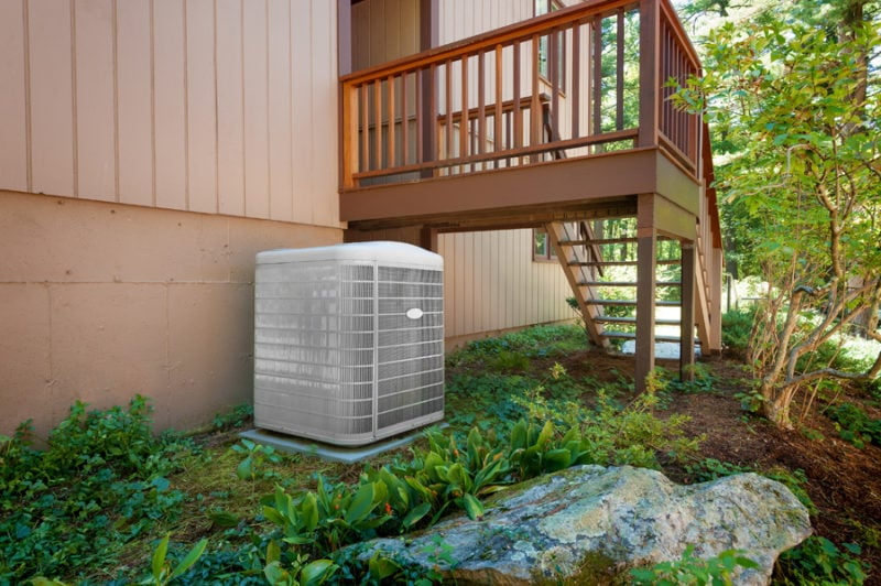 A residential heat pump central air conditioning and heating unit sitting outside a home.