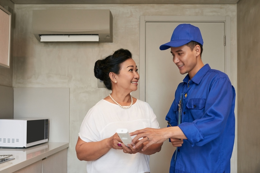 SmiIing technicial explaining Vietnamese senior woman how to use air conditioner remote control.