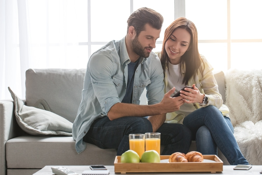 Young woman and man family couple indoors using smartphone.