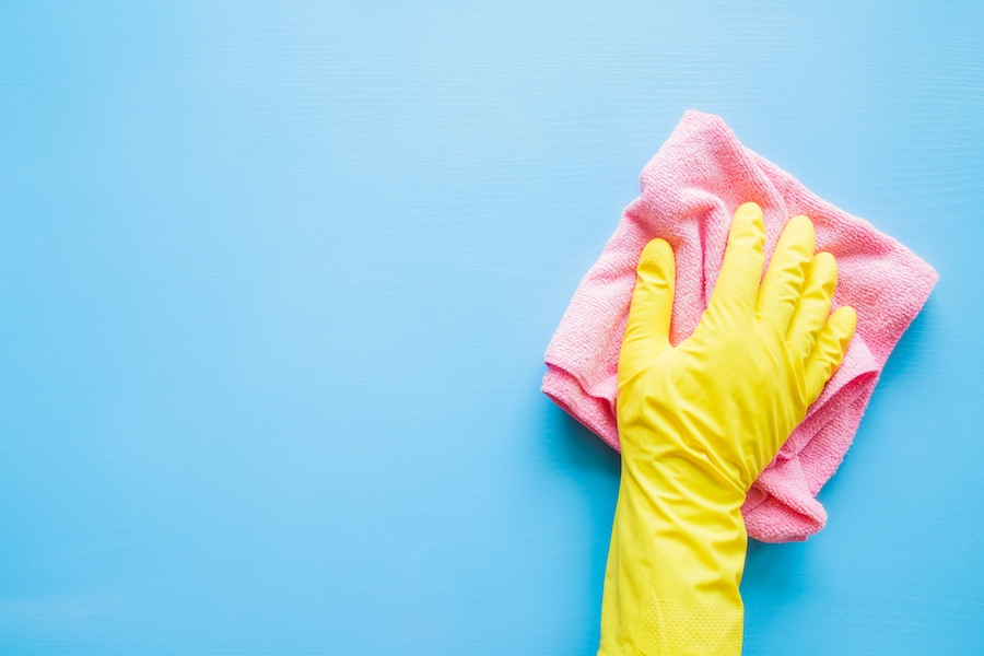 Yellow gloved hand washing a blue wall with a pink rag.